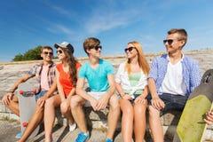 Groupe d'amis de sourire s'asseyant sur la rue de ville Photo stock