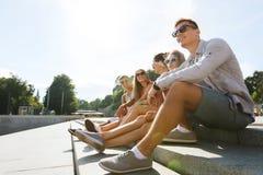 Groupe d'amis de sourire s'asseyant sur la rue de ville Image libre de droits