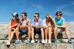 Groupe d'amis de sourire s'asseyant sur la rue de ville Images stock