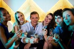 Groupe d'amis de sourire s'asseyant sur le sofa et ayant des verres de champagne Image libre de droits