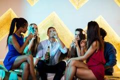 Groupe d'amis de sourire s'asseyant sur le sofa et ayant des verres de champagne Photos libres de droits