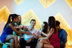 Groupe d'amis de sourire s'asseyant sur le sofa et ayant un verre de champagne Photographie stock libre de droits