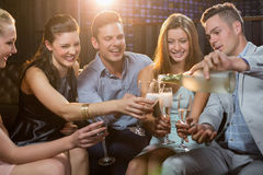 Groupe d'amis de sourire s'asseyant sur le sofa et ayant un verre de champagne Photos libres de droits
