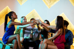 Groupe d'amis de sourire s'asseyant sur le sofa et grillant des verres de champagne Photo stock