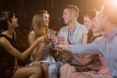 Groupe d'amis de sourire s'asseyant sur le sofa et grillant des verres de champagne Images stock