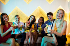 Groupe d'amis de sourire s'asseyant sur le sofa et montrant un verre de cocktail Images libres de droits