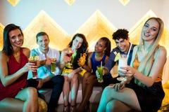Groupe d'amis de sourire s'asseyant sur le sofa et montrant un verre de cocktail Image libre de droits