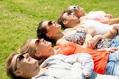 Groupe d'amis de sourire se trouvant sur l'herbe dehors Photographie stock libre de droits