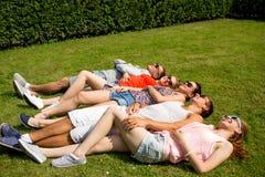 Groupe d'amis de sourire se trouvant sur l'herbe dehors Photographie stock