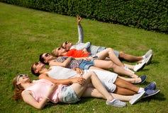 Groupe d'amis de sourire se trouvant sur l'herbe dehors Images stock