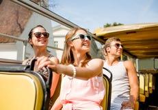 Groupe d'amis de sourire voyageant en bus touristique Photos stock