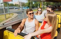 Groupe d'amis de sourire voyageant en bus touristique Image libre de droits