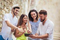 Groupe d'amis de touristes avec le comprimé numérique ayant l'amusement Photos stock