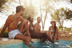 Groupe d'amis des vacances détendant à côté de la piscine extérieure Photo stock