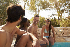 Groupe d'amis des vacances détendant à côté de la piscine extérieure Photo libre de droits