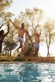 Groupe d'amis des vacances sautant dans la piscine extérieure Photo stock