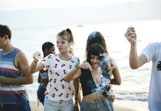 Groupe d'amis divers appréciant des cierges magiques au togethe de plage Photographie stock libre de droits