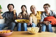 Groupe d'amis divers ayant une bière potable de soirée cinéma Photographie stock