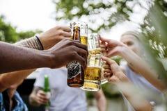 Groupe d'amis divers célébrant les bières potables ensemble Photos stock