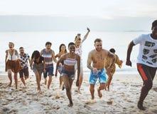 Groupe d'amis divers courant à la plage ensemble Image stock