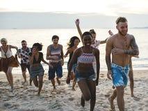 Groupe d'amis divers courant à la plage ensemble Images stock