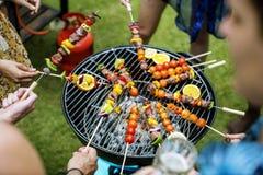 Groupe d'amis divers grillant le barbecue dehors Photographie stock libre de droits