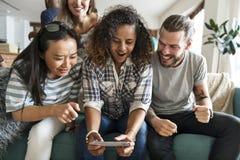Groupe d'amis divers jouant le jeu au téléphone portable Photographie stock