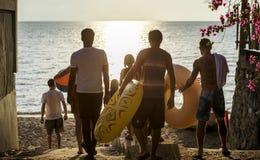Groupe d'amis divers marchant vers le bas à la plage avec l'inflatab Image libre de droits