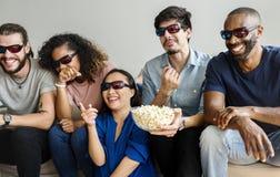 Groupe d'amis divers observant le film 3D ensemble Image stock
