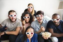 Groupe d'amis divers observant le film 3D ensemble Photos stock
