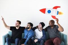 Groupe d'amis divers s'asseyant sur le divan Photos libres de droits
