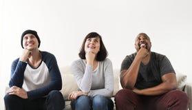 Groupe d'amis divers s'asseyant sur le divan Image libre de droits