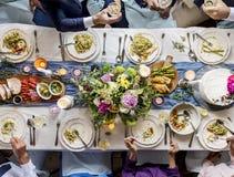 Groupe d'amis divers se réunissant ayant la nourriture ensemble Photo stock