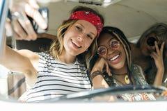 Groupe d'amis divers sur le voyage par la route prenant Selfie ensemble Image stock