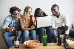 Groupe d'amis divers traînant et à l'aide des dispositifs numériques Photo libre de droits