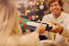 Groupe d'amis donnant des cadeaux de Noël à la maison Photos libres de droits
