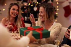 Groupe d'amis donnant des cadeaux de Noël à la maison Photo libre de droits
