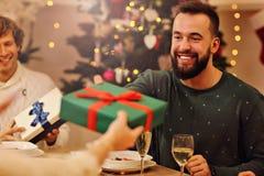 Groupe d'amis donnant des cadeaux de Noël à la maison Photographie stock libre de droits