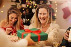 Groupe d'amis donnant des cadeaux de Noël à la maison Photo stock
