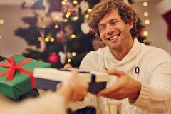 Groupe d'amis donnant des cadeaux de Noël à la maison Image stock