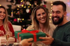 Groupe d'amis donnant des cadeaux de Noël à la maison Photographie stock