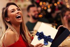 Groupe d'amis donnant des cadeaux de Noël à la maison Images stock
