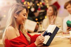 Groupe d'amis donnant des cadeaux de Noël à la maison Image libre de droits