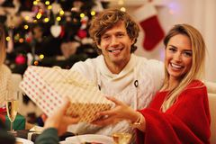 Groupe d'amis donnant des cadeaux de Noël à la maison Images libres de droits