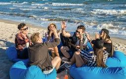 Groupe d'amis donnant la haute cinq sur la plage se reposant sur des fauteuils poire Photo libre de droits