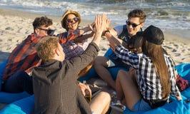 Groupe d'amis donnant la haute cinq sur la plage se reposant sur des fauteuils poire Images libres de droits