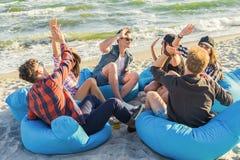Groupe d'amis donnant la haute cinq sur la plage se reposant sur des fauteuils poire Photographie stock libre de droits