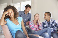 Groupe d'amis détendant sur Sofa At Home Together Photo stock