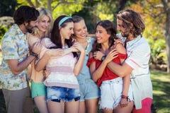 Groupe d'amis embrassant en parc Image libre de droits