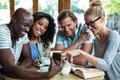 Groupe d'amis employant le mobile tout en ayant la tasse de café Photos libres de droits